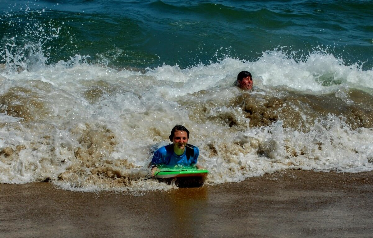Samantha Snyder and Melissa Thornton riding the waves at the 39t Street Beach.