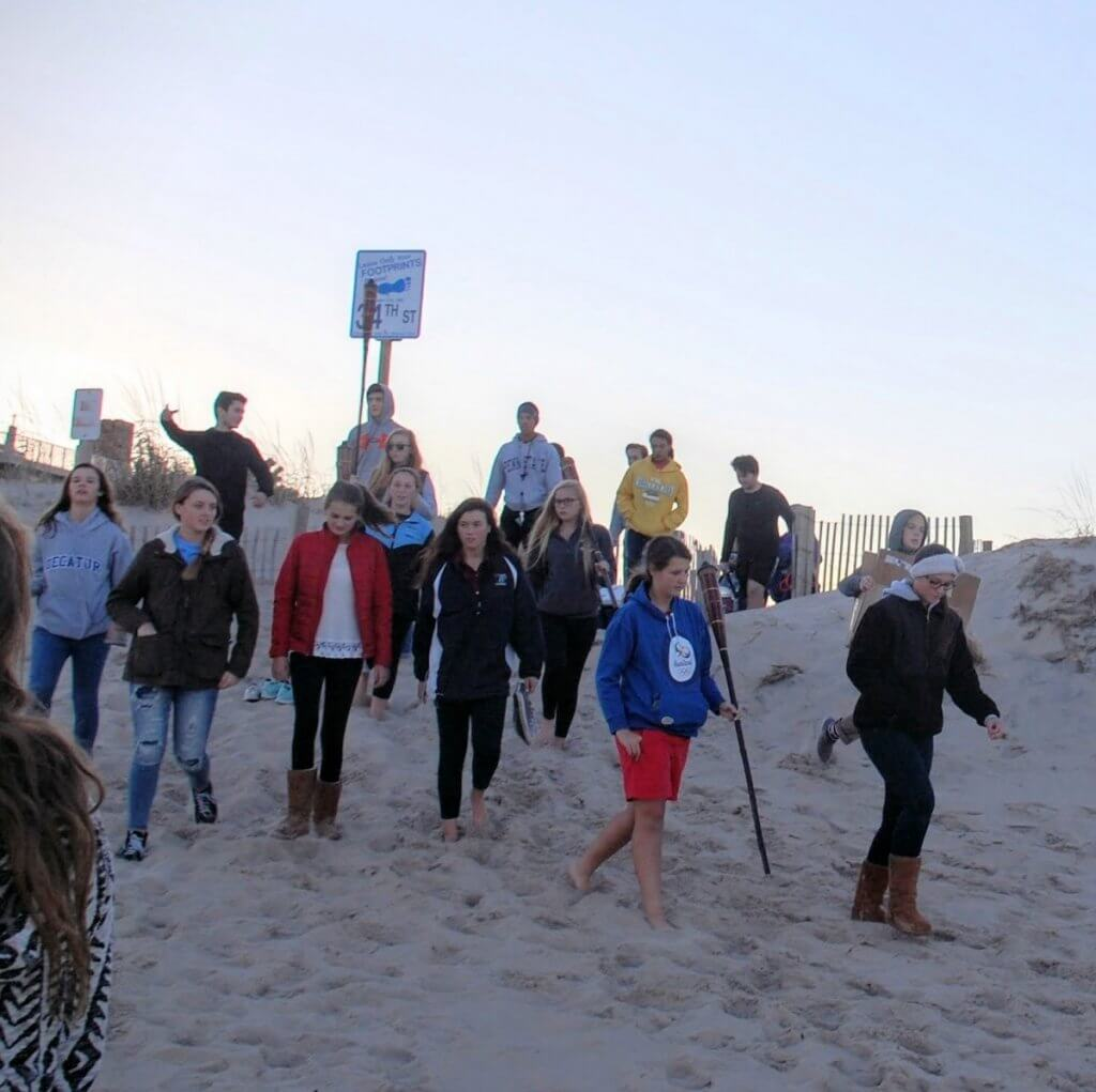 Members of the OCSC and Connections service group descend the dunes on their way to the bonfire following an afternoon of tidying up the beach.